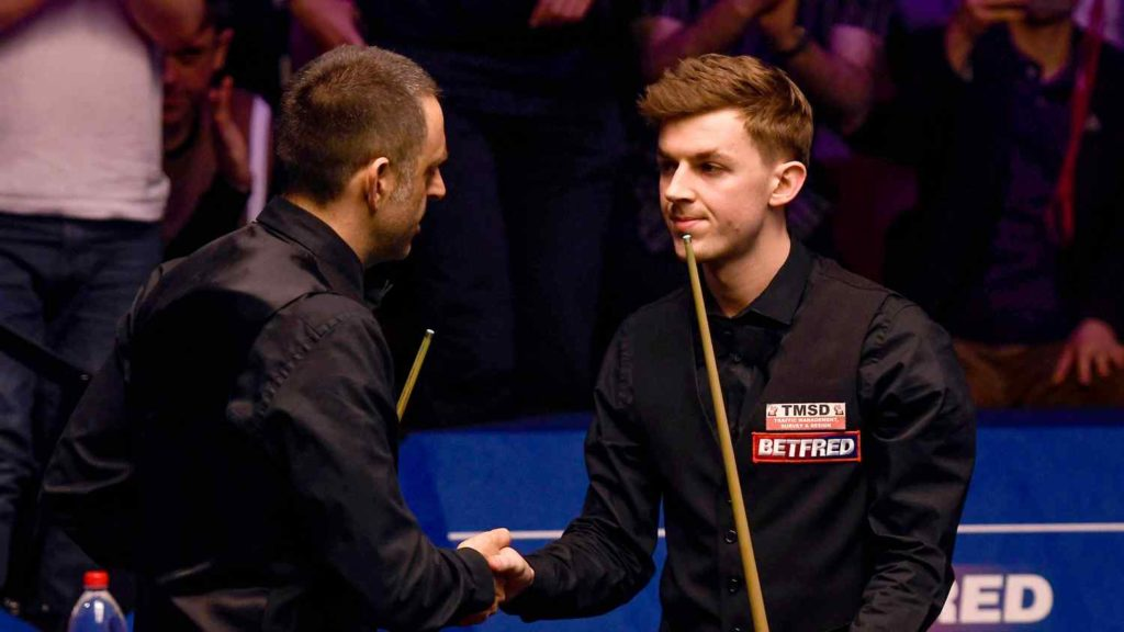 James Cahill shakes hands with world number one Ronnie O'Sullivan - after defeating him 10-8 in the first round of the 2019 Snooker World Championship.